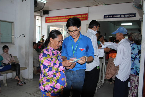 A student shows a woman how to fill in a form at the Can Tho Oncology Hospital in Can Tho City, southern Vietnam. Photo: Tuoi Tre