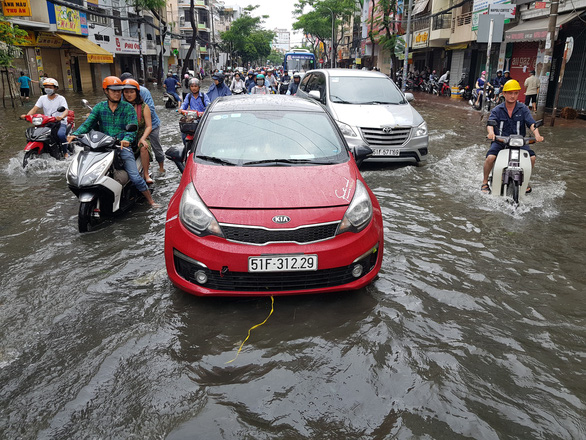 Vehicles plough through the floodwater in Ho Chi Minh City on November 26, 2018. Photo: Tuoi Tre