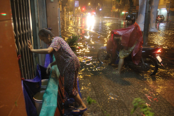 A resident builds a barricade to prevent floodwater from entering her house in Ho Chi Minh City on November 26, 2018. Photo: Tuoi Tre