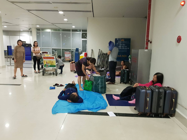 Passengers take a rest on raincoats at Tan Son Nhat International Airport in Ho Chi Minh City on November 25, 2018. Photo: Tuoi Tre
