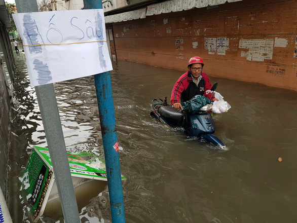 A commuter pushes their scooters through the floodwater in Ho Chi Minh City on November 26, 2018. Photo: Tuoi Tre