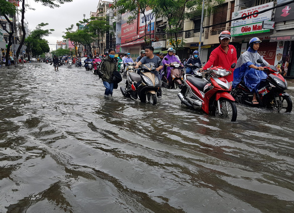 Commuters push their scooters through the floodwater in Ho Chi Minh City on November 26, 2018. Photo: Tuoi Tre