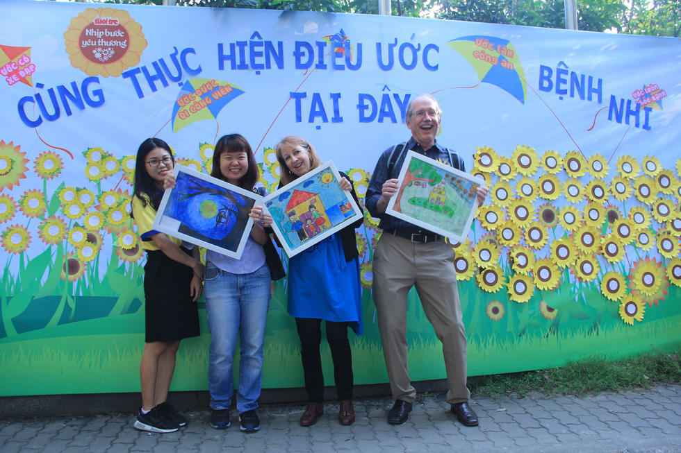 Two foreign tourists buy paintings at a fundraising booth. Photo: Duong Lieu / Tuoi Tre