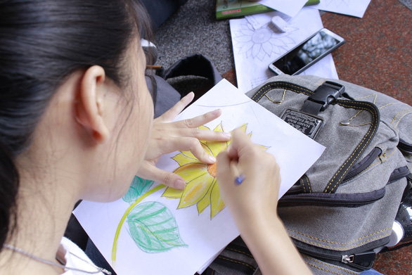"A participant draws a sunflower painting in response to the ""Toi dong hanh"" campaign. Photo: Tuoi Tre"