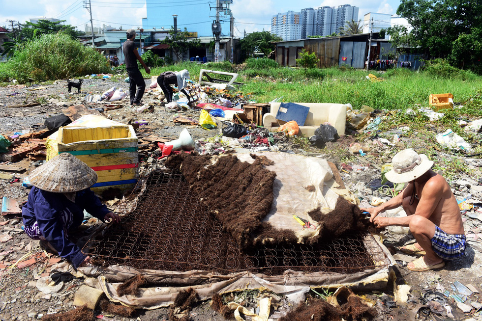 Damaged mattress and furniture are dumped on an empty land plot. Photo: Tuoi Tre