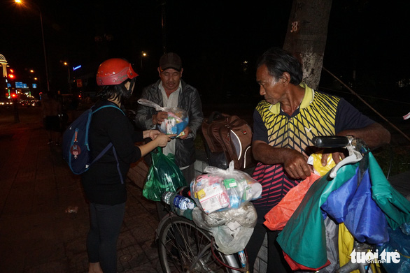 A woman hands presents to street people in Ho Chi Minh City, Vietnam. Photo: Tuoi Tre