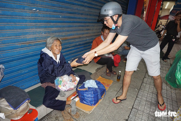 A man gives a gift to a homeless woman in Ho Chi Minh City, Vietnam. Photo: Tuoi Tre