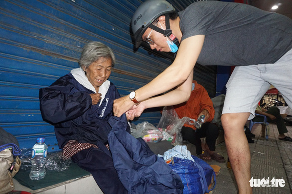 A man gives a jacket to a homeless woman in Ho Chi Minh City, Vietnam. Photo: Tuoi Tre