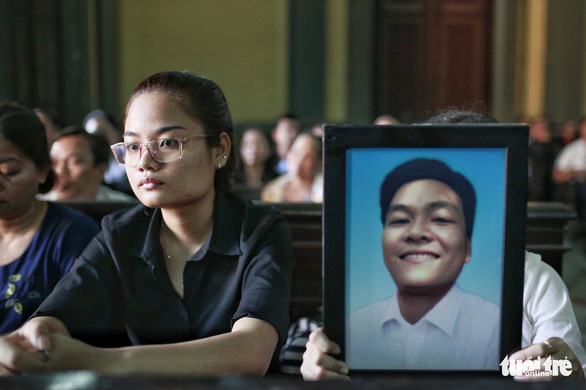 The fiancée of Nguyen Hoang Nam sits next to his portrait at the trial. Photo: Tuoi Tre