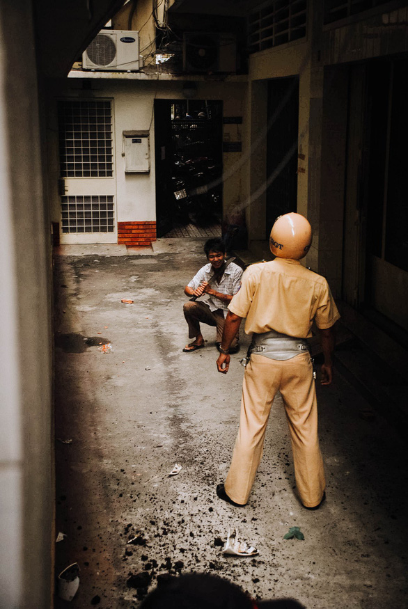 Nguyen Dang Thanh talks with a robber who is threatening to commit suicide in a cul-de-sac in Ho Chi Minh City, Vietnam, November 24, 2007. Photo: Dave MacMillan