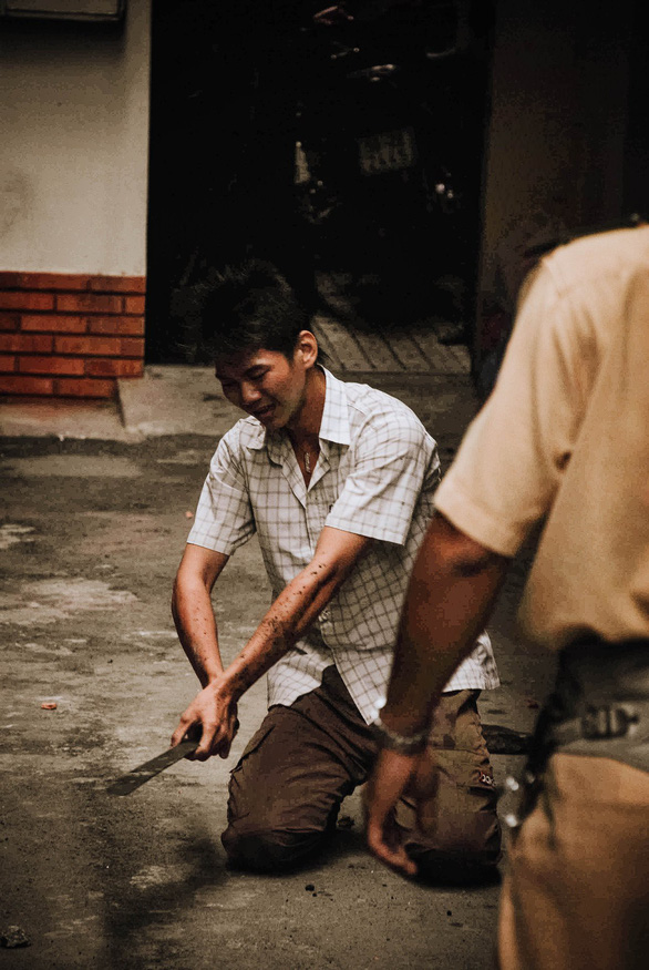The robber lays down a machete on the strength of Nguyen Dang Thanh's advice in a cul-de-sac in Ho Chi Minh City, Vietnam, November 24, 2007. Photo: Dave MacMillan