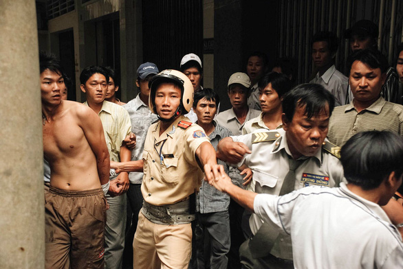 Nguyen Dang Thanh escorts a robber (shirtless) in Ho Chi Minh City, Vietnam, November 24, 2007. Photo: Dave MacMillan