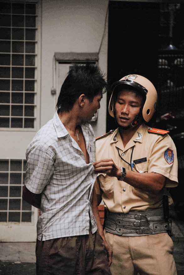 Nguyen Dang Thanh unbuttons a robber's shirt in an alley in Ho Chi Minh City, Vietnam, November 24, 2007. Photo: Dave MacMillan