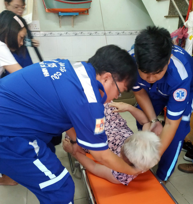 Doctors help an elderly patient onto a stretcher as they respond to an emergency call on a motorcycle. Photo: Tuoi Tre
