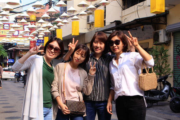 A group of visitors pose for a photo on Dao Duy Tu Street in Hanoi. Photo: Tuoi Tre