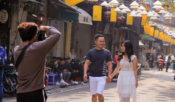 A couple poses for a photo on Dao Duy Tu Street in Hanoi. Photo: Tuoi Tre