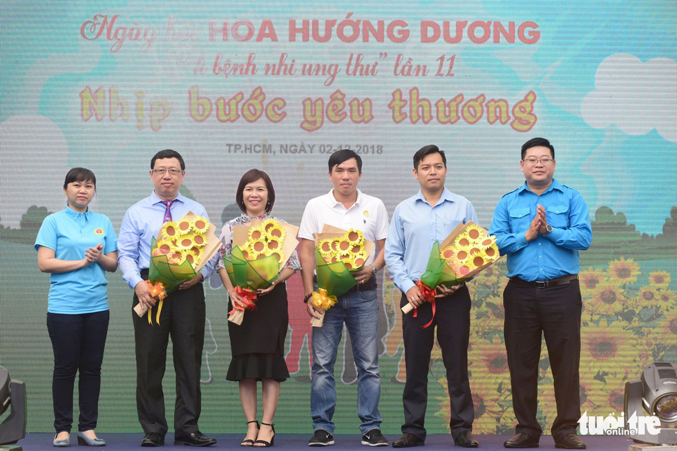 Ho Tan Dat (R), deputy head of the Vietnam Youth Federation, and Nguyen Thi Huong (L), member of Tuoi Tre's editorial board, gift flowers to the event's sponsors.