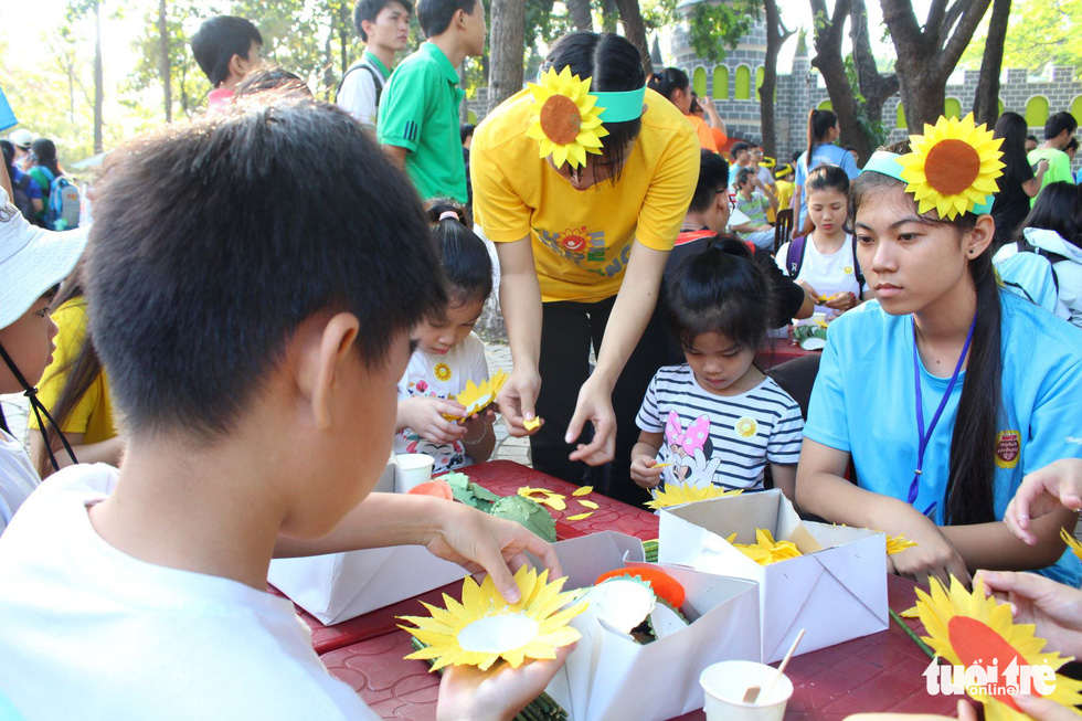 Participants make paper sunflowers at the festival.