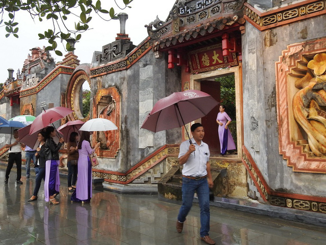 Visitors take pictures at the entrance gate of Ba Mu Temple in Hoi An City, central Vietnam, December 4, 2018. Photo: Tuoi Tre