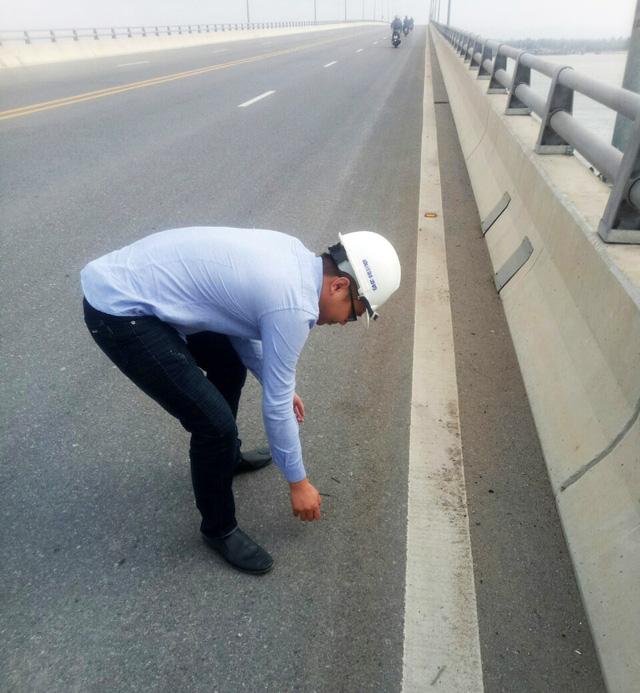 A road inspectors picks up nails on the Tan Vu – Lach Huyen sea bridge in Hai Phong City. Photo: Tuoi Tre