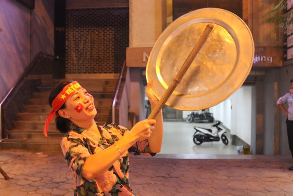 A fan uses kitchen utensils to make noises as she celebrates Vietnam's win against the Philippine on December 6, 2018. Photo: Tuoi Tre