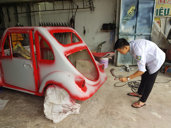 Ngo Viet Cuong sprays paint on his car chassis at his home-run repair shop in Nam Dinh Province, northern Vietnam. Photo: Ngo Viet Cuong