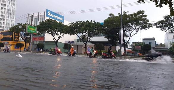 Vehicles travel along inundated Nguyen Huu Tho Street. Photo: Tuoi Tre