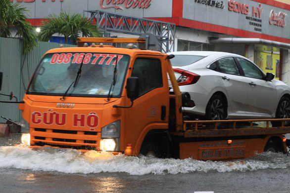 A rescue truck carries a car that breaks down due to rainwater. Photo: Tuoi Tre
