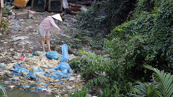 A resident dumps garbage along a trash-filled canal in District 8. Photo: Tuoi Tre