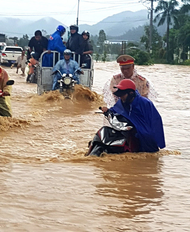 People struggle to travel on a flooded street in south-central Binh Dinh Province.