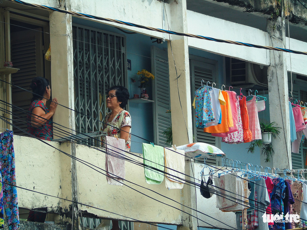 Next-door neighbors talk near hanging laundry at the Hang Phan apartment building in Ho Chi Minh City, Vietnam. Photo: Tuoi Tre