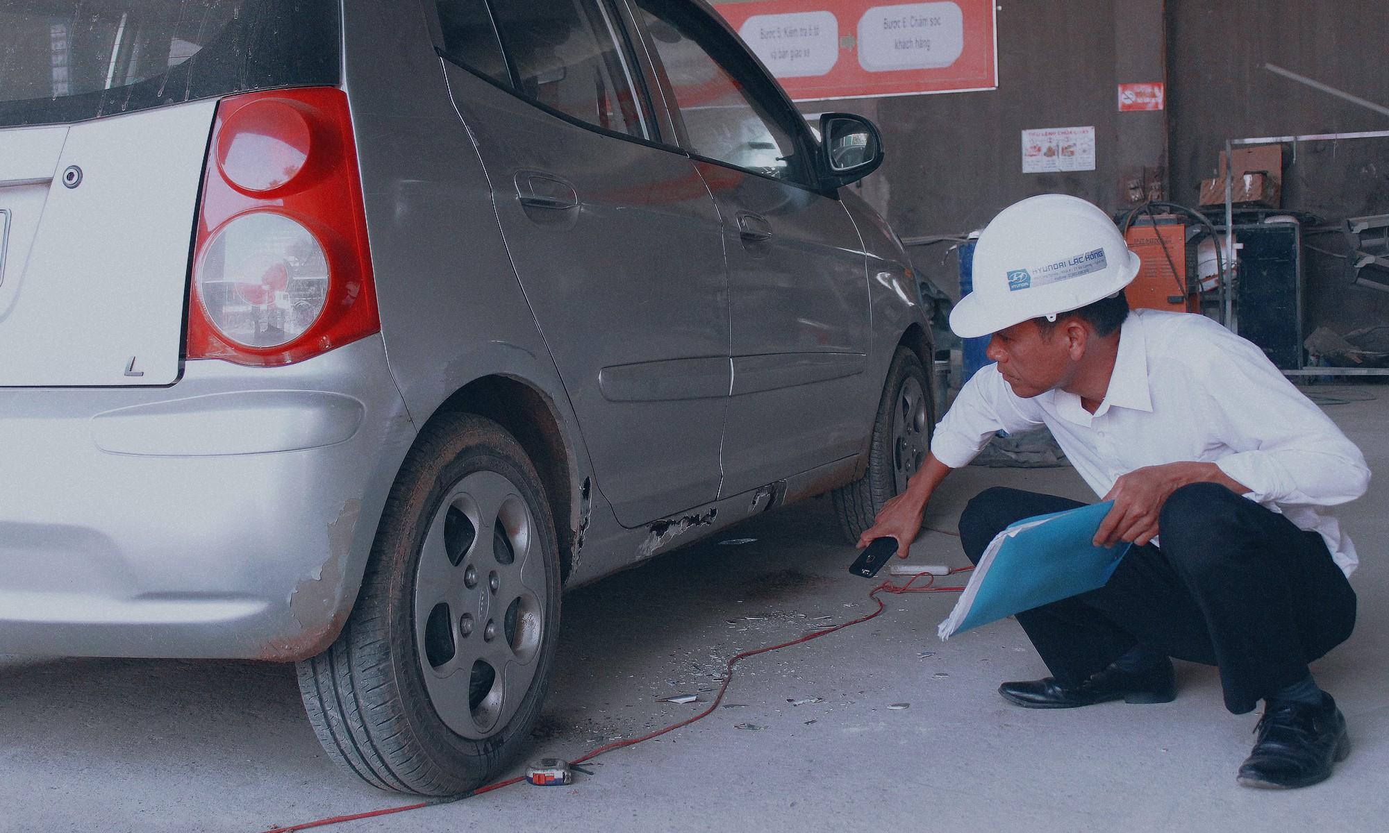 Dang Van The performs a car damage inspection. Photo: Tuoi Tre