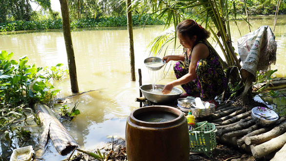 A woman washes the dishes along a brackish river in Dong Thap Province, southwestern Vietnam. Photo: Tuoi Tre