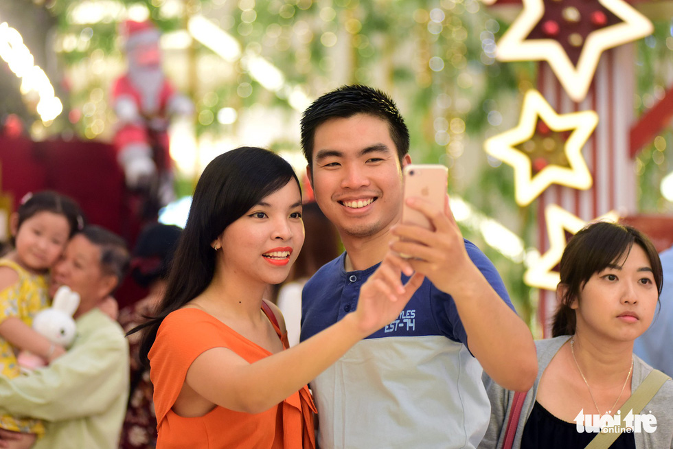 A couple takes a selfie at a shopping mall. Photo: Tuoi Tre