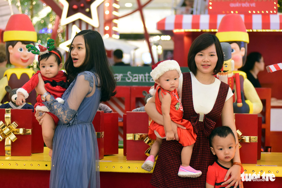 Women and their children pose for a Christmas photo. Photo: Tuoi Tre