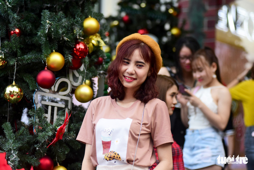 A young girl poses by a Christmas tree. Photo: Tuoi Tre