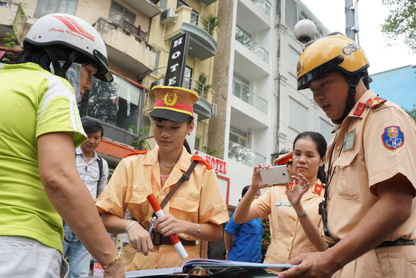A policeman shows a student how to book a violator in Ho Chi Minh City, Vietnam, December 22, 2018. Photo: Tuoi Tre