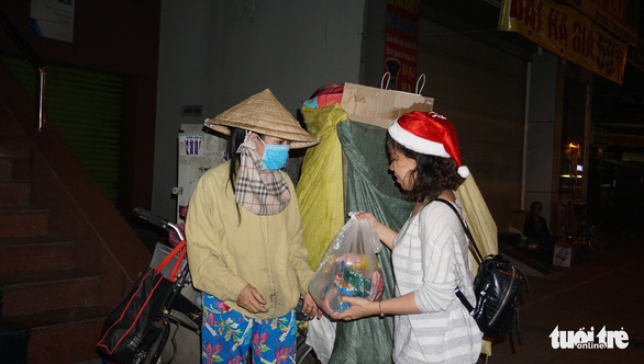 A woman wearing a Santa hat gives gifts to a scrap dealer in Ho Chi Minh City, Vietnam, December 24, 2018. Photo: Tuoi Tre