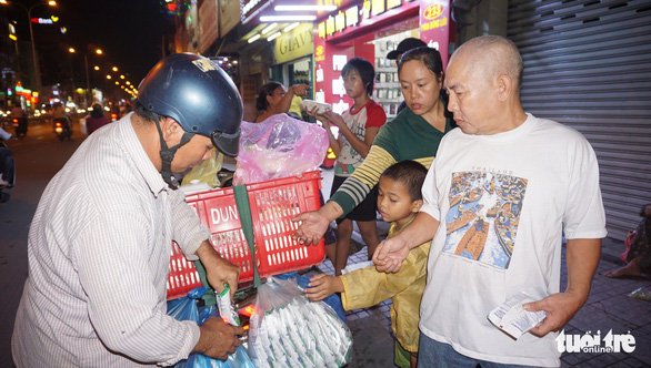 Vo To Phuong hands a box of rice and grilled pork to people in difficult situations along Phan Dang Luu Street in Ho Chi Minh City, Vietnam, December 24, 2018. Photo: Tuoi Tre