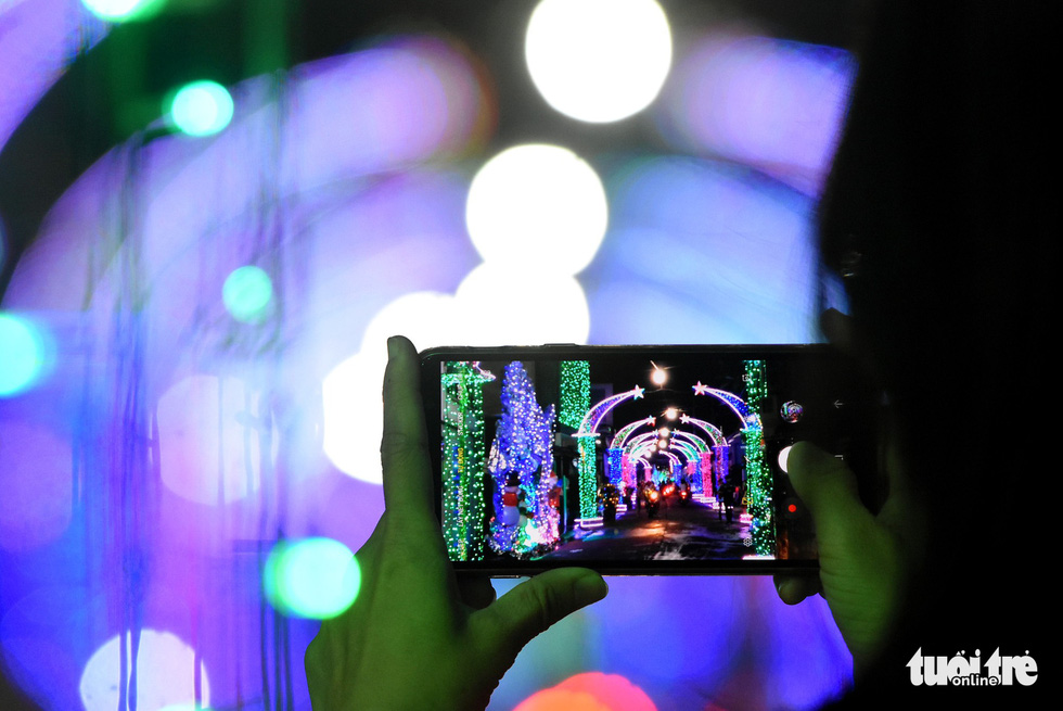 A visitor takes a photo of a street lightened up with decorative lights in the southern province of Dong Nai. Photo: Tuoi Tre