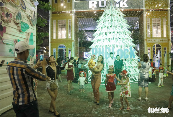 Visitors pose for photos with the 8-meter Christmas tree made up of 200 plastic chairs at the Rubik Zoo in Ho Chi Minh City. Photo: Tuoi Tre