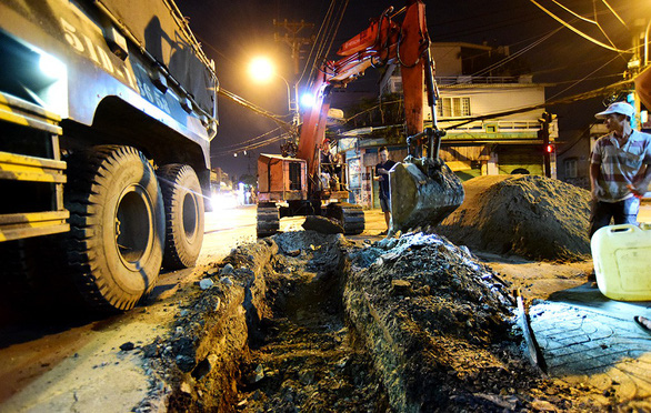 An excavator digs into a road in Ho Chi Minh City for the installation of underground power lines. Photo: Tuoi Tre