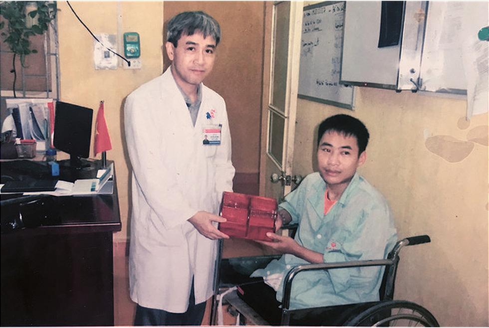 Pham Van Hao is seen beside a doctor who helped him in this provided photo.