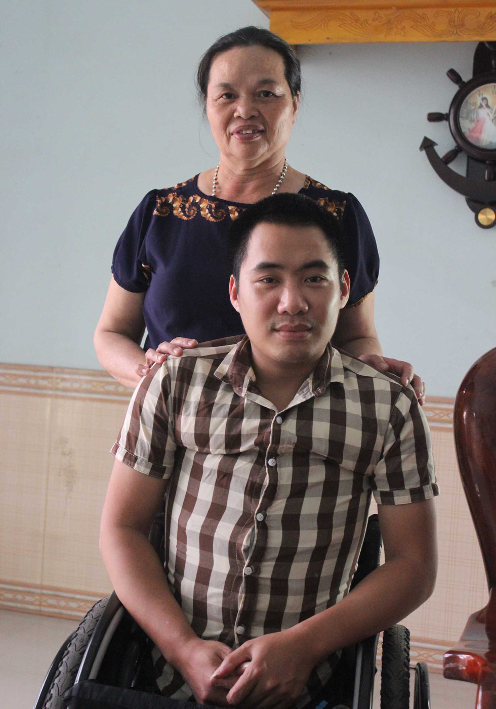Dinh Thi Thuong (standing) and her foster son, Dinh Van Hao, are seen at their home in Thai Nguyen Province, northern Vietnam. Photo: Tuoi Tre