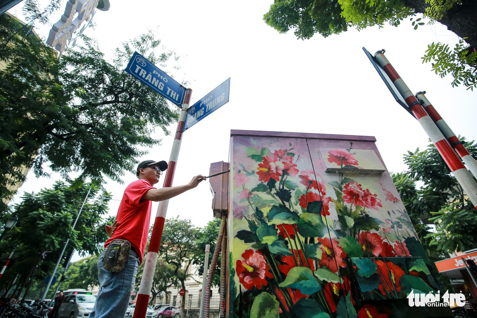 A Hanoi Art Space member paints an electric cabinet on Trang Thi Street. Photo: Tuoi Tre