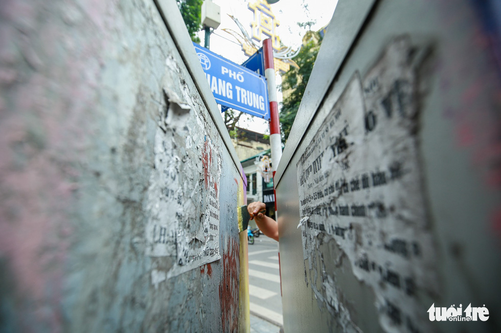An electric cabinet is covered by distorted bill posters. Photo: Tuoi Tre