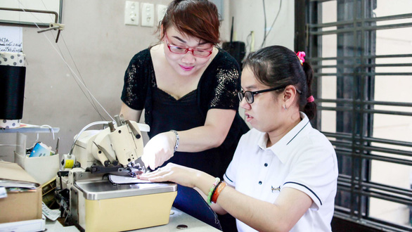 Nguyen Thi Thuy Hoa teaches a disabled girl to sew a in Ho Chi Minh City, Vietnam. Photo: Tuoi Tre