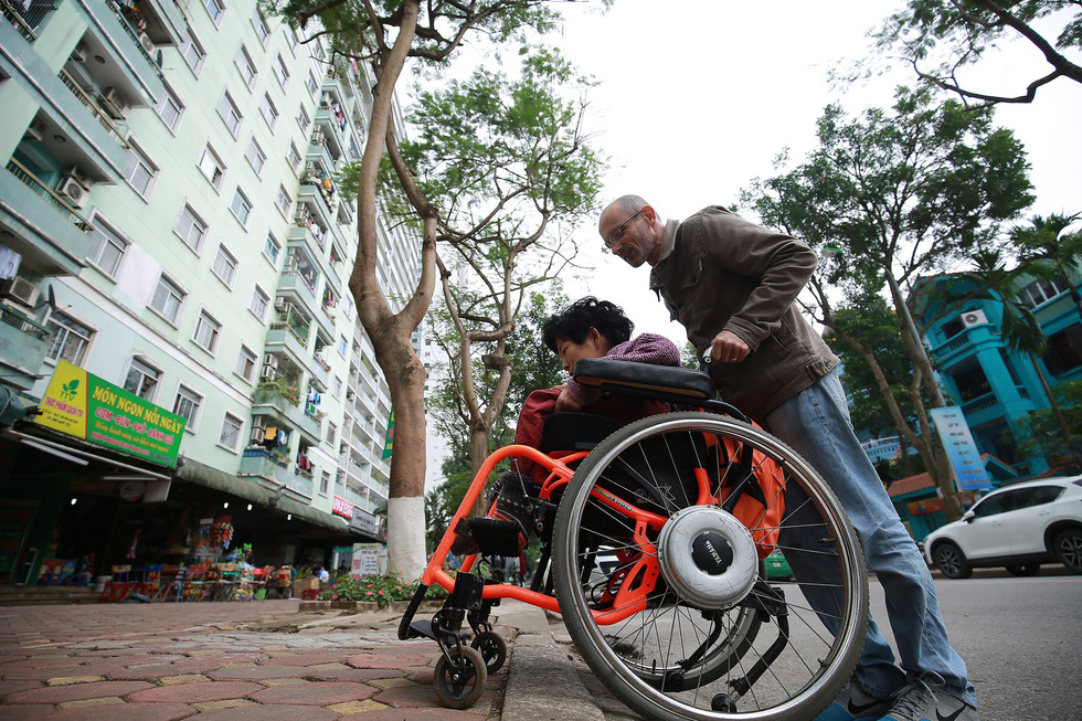 Neil Bowden Laurence and Nguyen Thi Van in her wheelchair along a street in Hanoi, Vietnam. Photo: Tuoi Tre