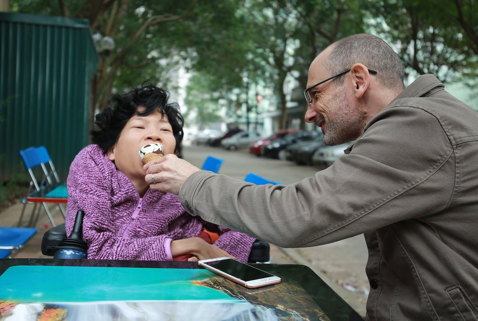 Neil Bowden Laurence helps Nguyen Thi Van eat ice cream