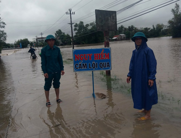 Men stand next to a traffic-banning sign along an inundated road in Phu Yen Province, southcentral Vietnam, December 29, 2018. Photo: Tuoi Tre
